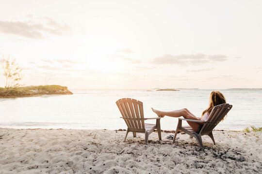 Woman relaxing on chair at beach against sky during sunset