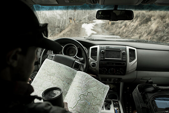 Man reading map while traveling in car