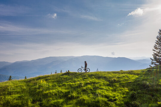 Mountain biker on his bike on a green hill on a sunny day