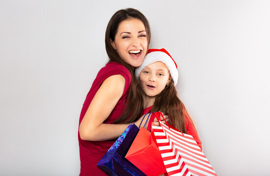 Happy laughing excited mother with open mouth hugging with love her cute joying daughter in santa clause hat and holding Christmas present packages