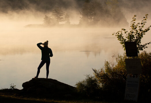 Young woman looks over sunrise on fog covered Vermont Lake