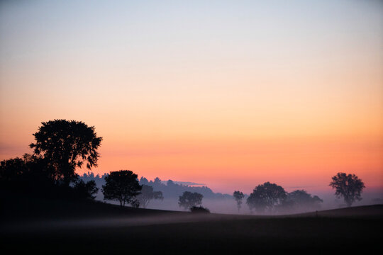Dawns early light illuminates morning ground fog on country farm scene