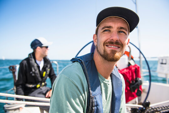 Man smiling during a family sail on sunny summer day
