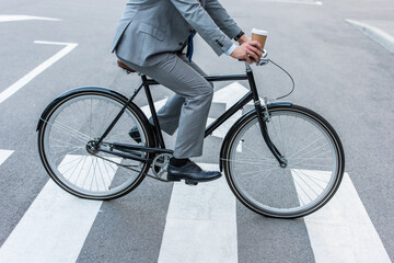 Cropped view of businessman holding takeaway coffee while cycling on crosswalk