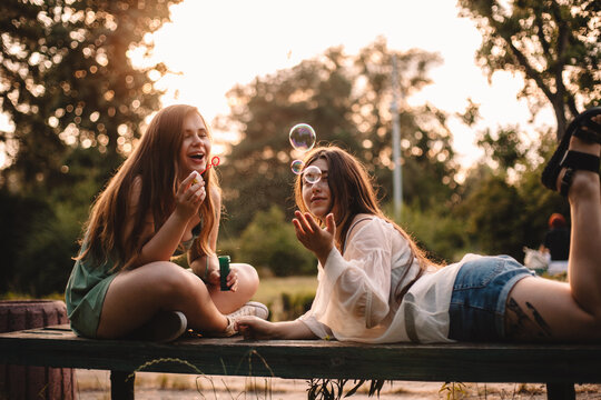 Happy lesbian couple playing with bubbles relaxing in park in summer