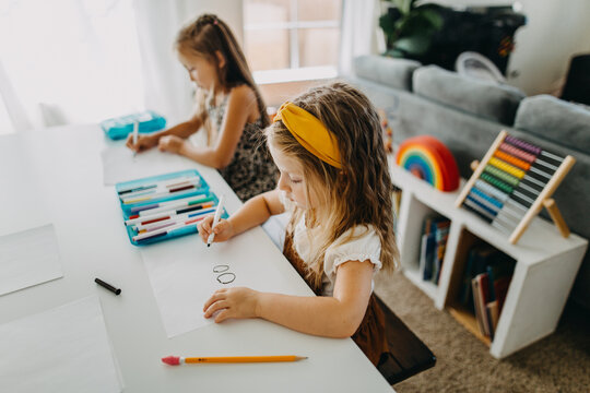 Two young girls drawing with colorful markers at table
