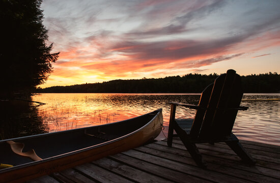 Canoe and adirondack chair on a dock on a lake at sunrise.