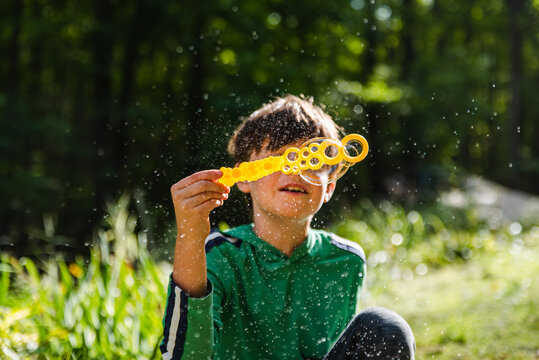 Young boy blowing soap bubbles with a large wand outdoors.