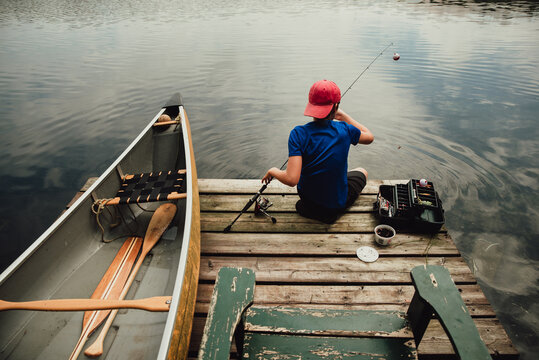 Teen boy fishing from a dock on a lake with tackle box in the summer.
