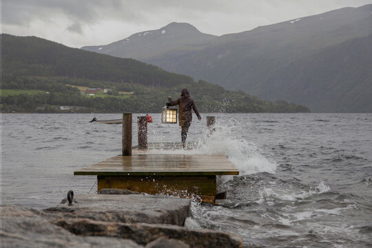 A person carrying a lantern at the edge of a dock in Norway
