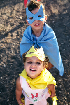 children disguised as superheroes to play in the field, are watching o