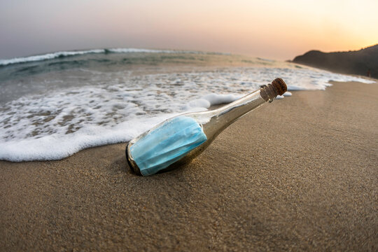 Surgical face mask inside a glass bottle at the beach