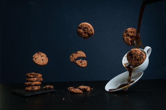 Horizontal image of flying cookies falling on a cup of coffee