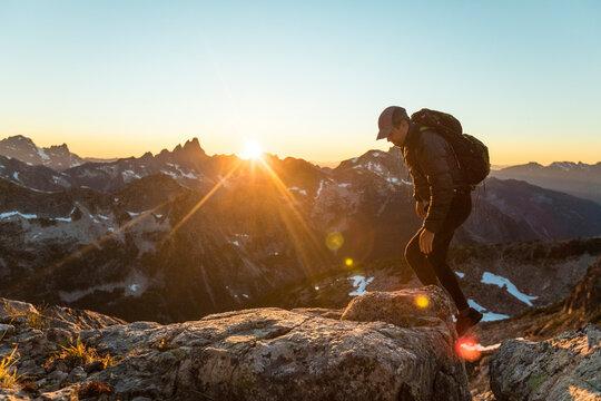 Backpacker scrambling over rocky terrain to reach mountain summit.