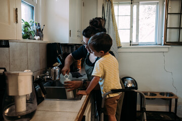Mother and Child working together at kitchen sink