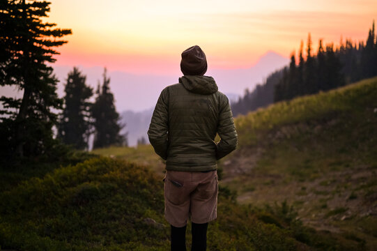 Back view of hiker in puffy coat watching a colorful sunset