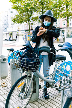 Young woman with mask chooses bicycle at a public rental point