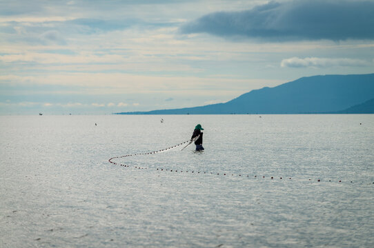 Fisherman lays net in the shallow waters of the sea. Kampot province, Cambodia.
