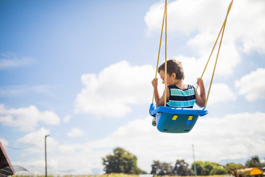 Low angle view of boy swinging outdoors on blue swing at playground.