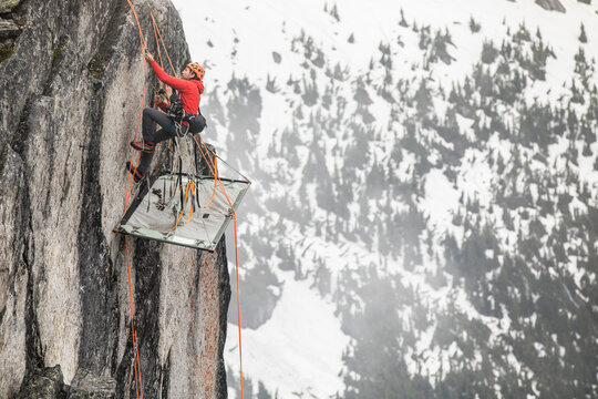 Rock climber uses prusik to ascend cliff above portaledge.