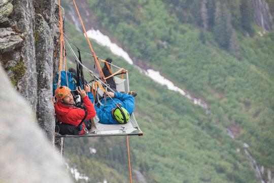 Portrait of rock climbers using portaledge during climbing trip.
