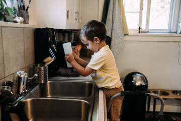 Little boy playing with squirt bottle at kitchen sink