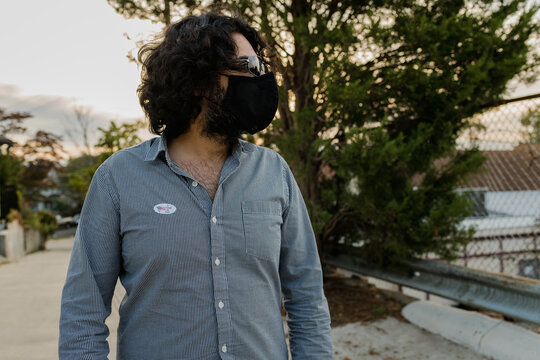 Man with mask and I voted sticker looking off camera