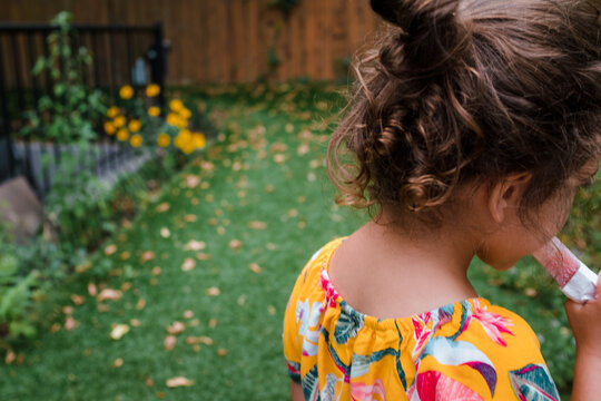 Little girl with curly hair eating a popsicle outside