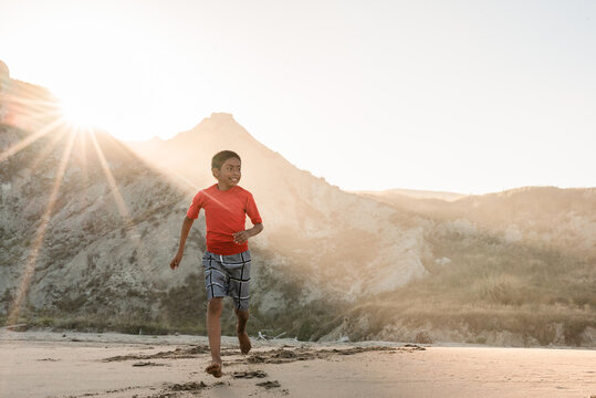 Latino tween boy running on beach with mountains in background