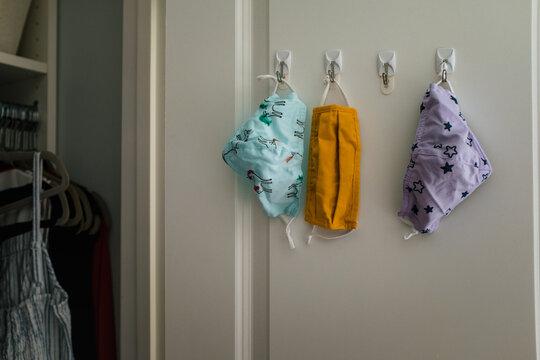 three cloth masks hanging on hooks in closet