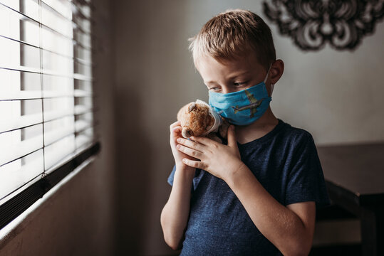 Close up of young school aged boy with mask on with stuffed animal