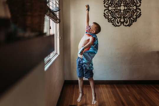 Young boy dressed as super hero with mask standing by window at home