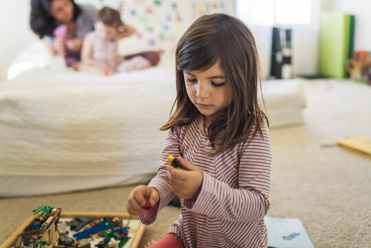 Young old girl wearing striped shirt on floor playing with Legos