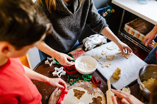 Top view family making Christmas cookies on parchment paper on tray