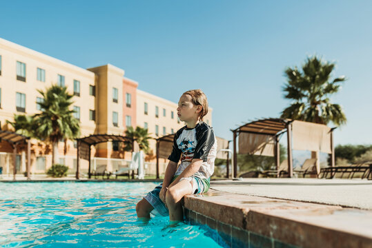 Young boy sitting on side of pool on vacation in Palm Springs