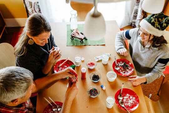 Top view cheerful family decorating together chirtsmas cookies