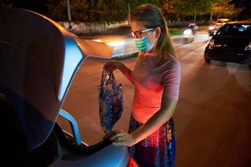 A woman put her belonging to the car trunk after shopping during COVID Fotomurales