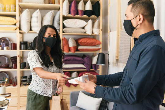 Woman with mask on checking out with credit card at home decor store