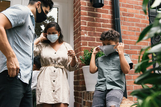 Family and young son putting on masks to go out of brownstone home