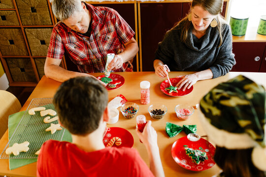 Top view family decorating sugar cookies holiday on table at home