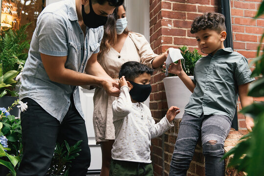 Parents helping young kids put on masks before going out of home