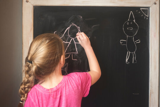 Young girl drawing with chalk on a blackboard