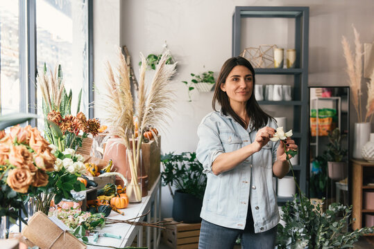 Florist stylizing single rose in her flower shop and building bouquet