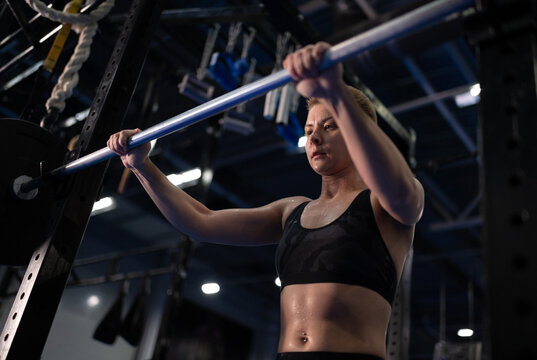 Exhausted female athlete taking barbell from rack