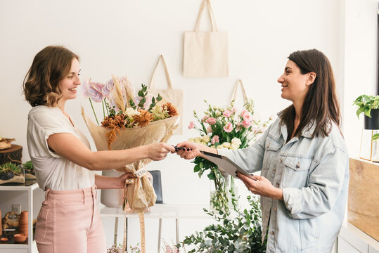 Smiling you woman handing credit payment to woman business owner