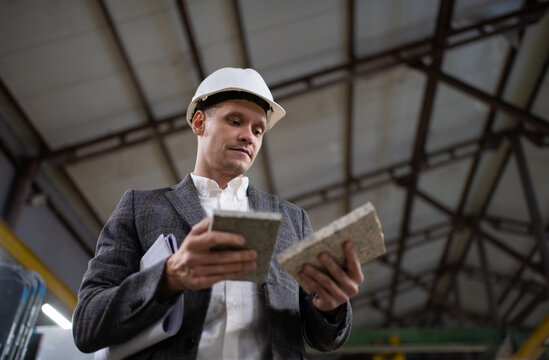 Male worker of factory picking marble samples