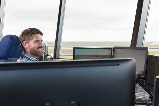 Bearded dispatcher controlling flights in airport
