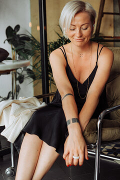 Blond stylish woman in black dress sitting in arm chair looking down