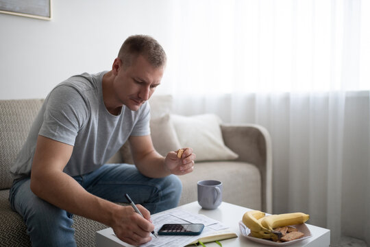 Adult man snacking and doing paperwork