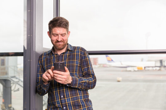 Cheerful man using smartphone in airport